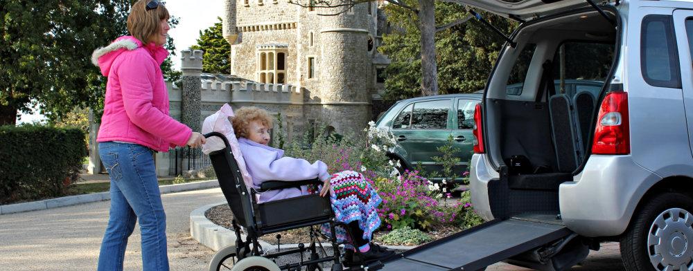woman assisting elderly woman in getting inside the van