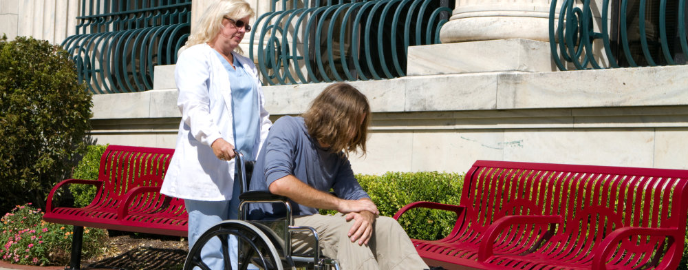 woman assisting man in a wheelchair