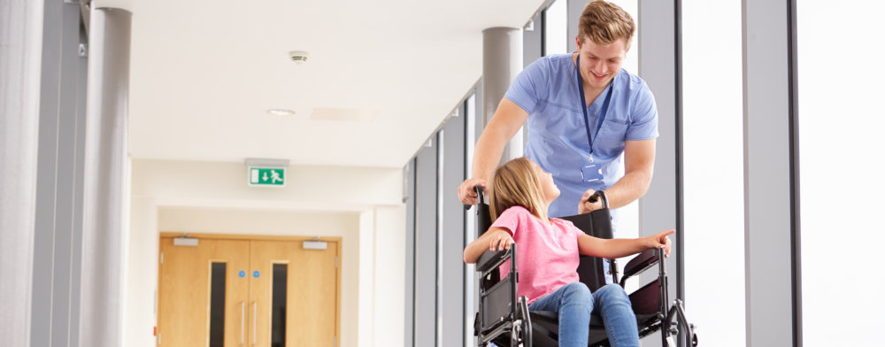 caregiver assisting the child in a wheelchair