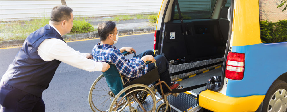 driver assisting elderly man in a wheelchair